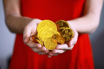 woman holding gold coins